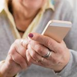 Older woman tapping on cell phone