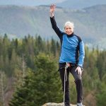 Woman with arm raised after climbing top of mountain