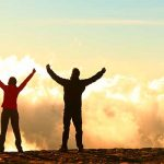 2 people arms raised on top of mountain
